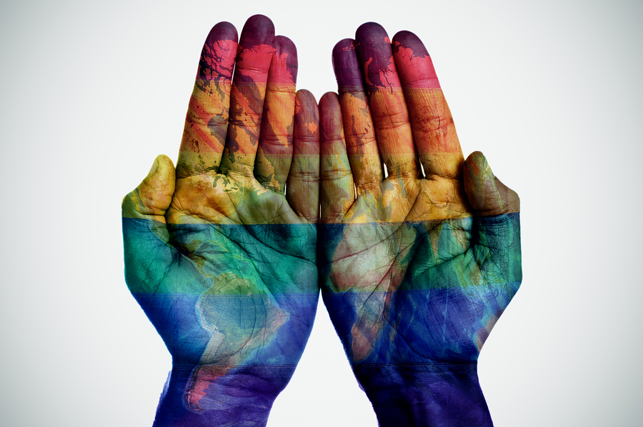 lgbtq rainbow pride painted as the world on hands