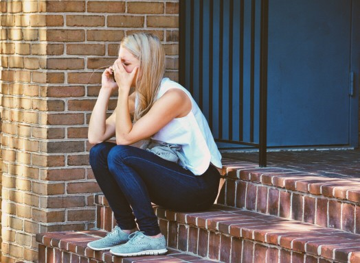 image of a woman sitting on steps crying.