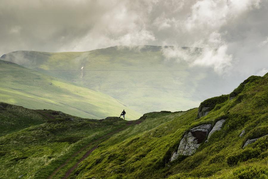 landscape shot of a hiker on a mountain ridge.